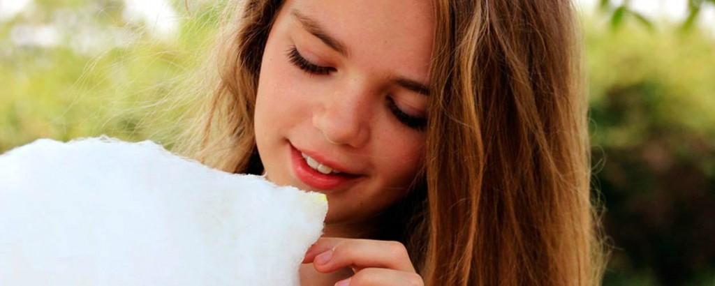 Niña sonriendo con un algodón de azucar